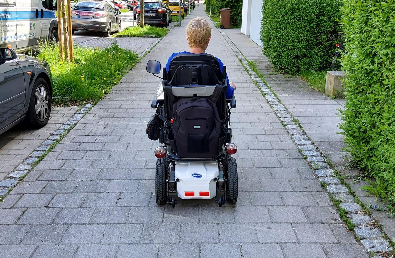 Person operating a motorized wheelchair down city cobblestone sidewalk